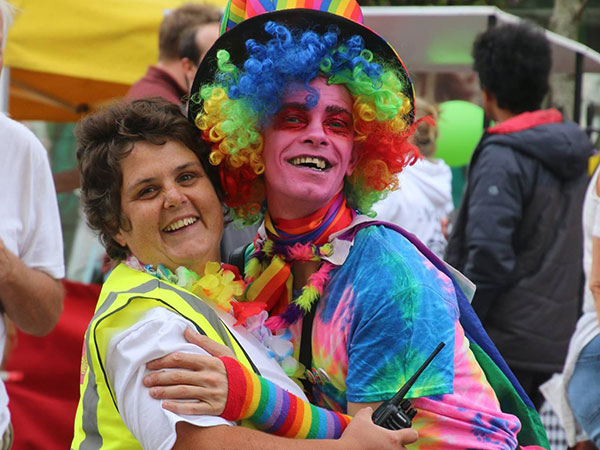 Colour clash love up! – A rainbow coloured Pride participant hugs one of the stewards in her hi-vis vest